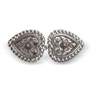 Mestergull Hjerteformet capespenne i oksidert sølv, dekorert med kruse og filigran. Denne spennen brukes blant annet i Nordhordland, Sogn og Vest-Oppland. NORSK BUNADSØLV Spenne