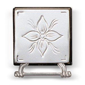 Mestergull Blank veskestøl i hvitt sølv til Rogalandsbunaden. Den har gravert dekor som harmonerer med det vakre florabroderiet på bunaden. Monteres på svart skinnlist ved hjelp av monteringsringene på baksiden. NORSK BUNADSØLV Belte