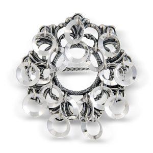 Mestergull Sølje i oksidert sølv med støpt bunn dekorert med raslende ringløvv. Den blir brukt på Trønderbunaden og festes på bringa. NORSK BUNADSØLV Sølje