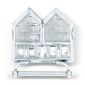 Mestergull Veskestøl i hvitt sølv til den lyse Bergensbunaden. Motivet av Bryggen, det mest kjente landemerket i byen, pryder veskestølen. NORSK BUNADSØLV Belte