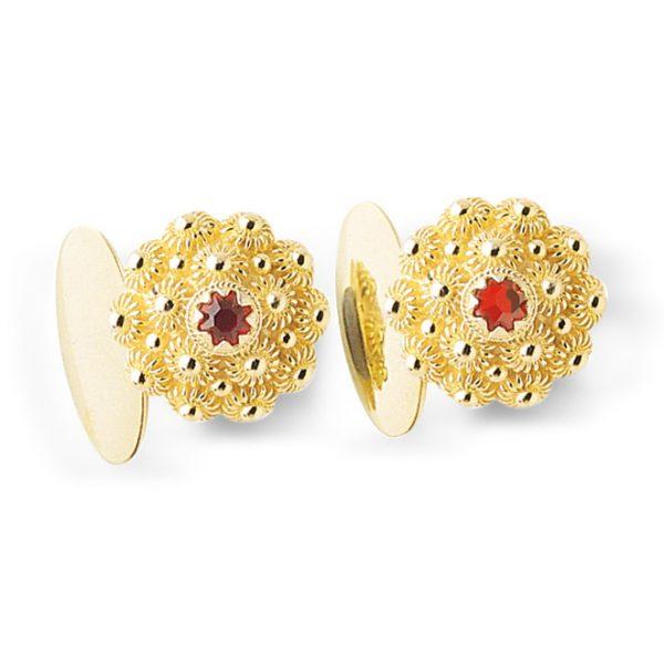 Mestergull Forgylte mansjettknapper i forgylt sølv med dekorative kruser og rød sten til Fanabunaden, både til dame og herre. Mansjettknappene har bakstykke med bunn som gjør dem kraftigare. NORSK BUNADSØLV Mansjettknapp