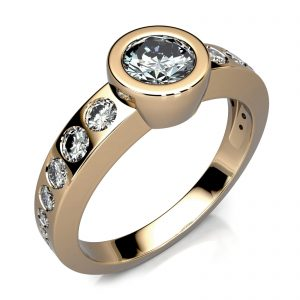 Mestergull Ring i gult gull 585 med sariefattet diamant i midten og mindre stener i forløp på ringens skuldre. Ringen er spesiallaget etter kundens spesifikasjoner. DESIGN STUDIO Spesialdesign Ring