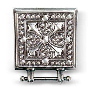 Mestergull Veskestøl i oksidert sølv med kort hempe til veska. Motivet med diagonalkorste finner vi igjen i mye av bunadsølvet rundt om i landet, og denne typen beltestøler har gjennom generasjoner vært den mest brukte. NORSK BUNADSØLV Belte
