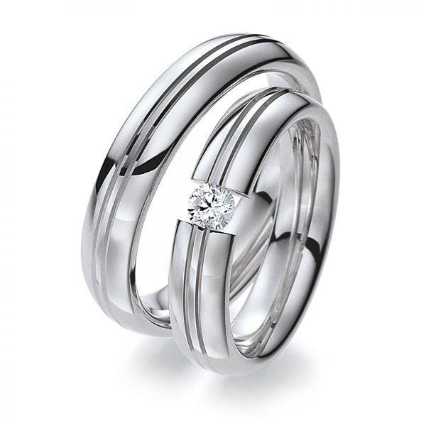 """Mestergull Dette ringparet kombinerer hvitt gull i profil 1 med diamantskåret mønster og diamant fattet i dameringen som en """"spennring"""". Prisen nedenfor er pr. ring uten diamant da denne kan velges i mange størrelser. LYKKERINGENE Eksempel Ring"""