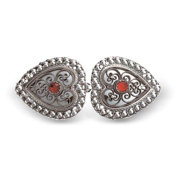Mestergull Hjerteformet capespenne i oksidert sølv med rød sten, dekorert med kruse og filigran. NORSK BUNADSØLV Spenne