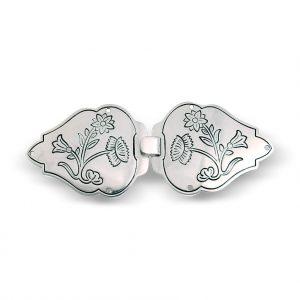 Mestergull Capespenne i oksidert sølv til Nordlandsbunad. Den har et blomstermotiv som tar utgangspunktet i broderiet på bunaden, og er preget inn i spenna. NORSK BUNADSØLV Spenne