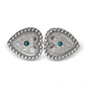 Mestergull Hjerteformet beltespenne i blankt og oksidert sølv med grønn sten for montering på skinnlist. Spennen er omkranset med perlekant og filigrandekor med kruse i midten. NORSK BUNADSØLV Spenne