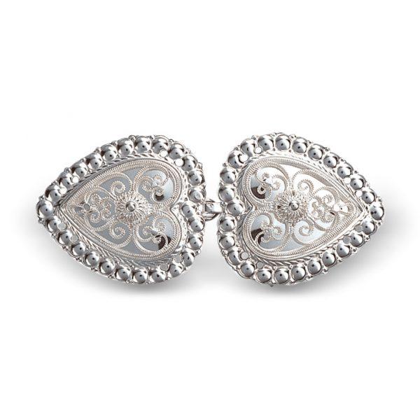 Mestergull Hjerteformet capespenne i hvitt sølv, dekorert med kruse og filigran. NORSK BUNADSØLV Spenne