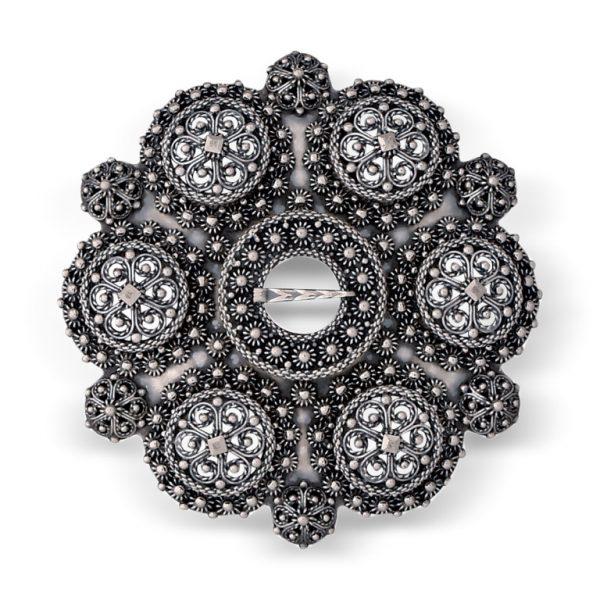 Mestergull Nydeleg bolesølje i oksidert sølv til bunader i Telemark. Den er laget med 6 store og seks små knapperoser som utgjør bolene på sølja. Ekstra sikkerhetslås på baksiden. NORSK BUNADSØLV Sølje