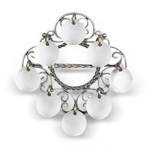 Mestergull Liten nordlandssølje i oksidert sølv. Den har en særegen firkanatet søljebunn prydet med 8 glatte, blinkende løv. NORSK BUNADSØLV Sølje