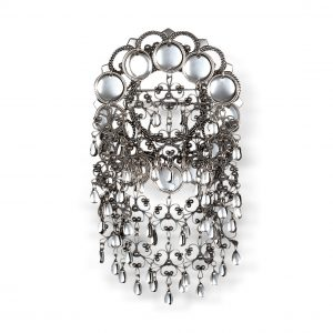 Mestergull Denne sølja er i oksidert sølv med støpt filigranbunn og dekorative, raslande heng. Blanke trådkantløv omkranser den åpne ringen i midten. NORSK BUNADSØLV Sølje