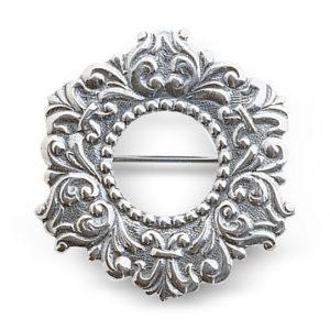 Mestergull Liten halsring i oksidert sølv til Vestfoldbunaden. Opphavet til liljemotivet på sølja kan spores tilbake til 1800-talet og en spenne som ble funne utanfor Mariakirken i midten av 1800-talet. NORSK BUNADSØLV Halsknapp