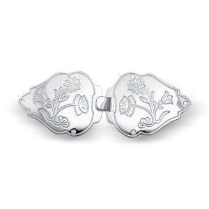 Mestergull Vestspenne i hvitt sølv til Nordlandsbunaden. Blomstermotivet er preget inn og tar utgangspunkt i broderiet på bunaden. NORSK BUNADSØLV Spenne