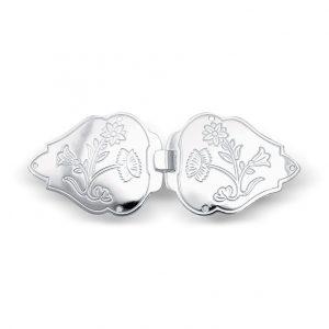 Mestergull Capespenne i hvitt sølv til Nordlandsbunad. Den har et blomstermotiv som tar utgangspunktet i broderiet på bunaden, og er preget inn i spenna. NORSK BUNADSØLV Spenne
