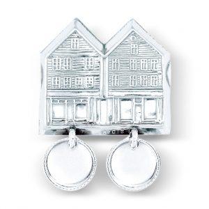 Mestergull Beltestøl med trådkantløv i hvitt sølv til den lyse Bergensbunaden. Motivet av Bryggen, det mest kjente landemerket i byen, pryder beltestølen. NORSK BUNADSØLV Belte