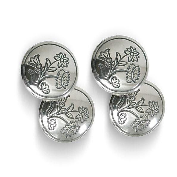 Mestergull Doble mansjettknapper i oksidert sølv til Nordlandsbunad med gravert blomstermotiv som tar utgangspunkt i broderiet på bunaden. Finst også i kvitt sølv. NORSK BUNADSØLV Mansjettknapp