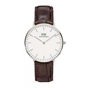 Mestergull Det er vanskelig å ikke like denne perfekt utformede klokken med en rem i vakkert, mørkebrunt krokodillepreget mønster, hvit urskive og en smal og tynn urkasse på 6 mm DANIEL WELLINGTON Ur