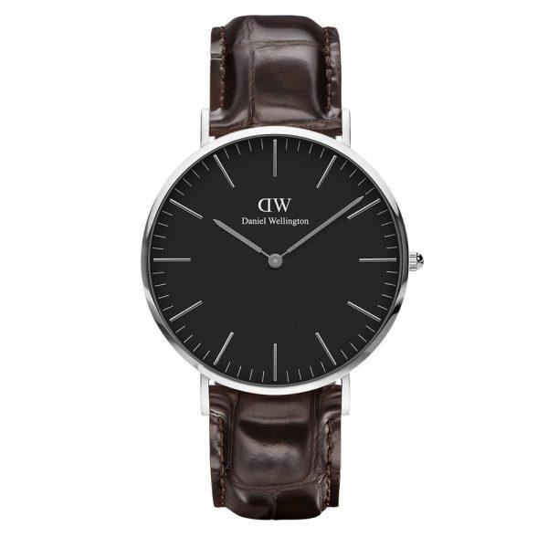Mestergull Det er vanskelig å ikke like denne perfekt utformede klokken med en rem i vakkert, mørkebrunt krokodillepreget mønster, sort urskive og en smal og tynn urkasse på 6 mm. Classic Black York er inspirert av en enklere tid og er laget for å vare. DANIEL WELLINGTON Ur
