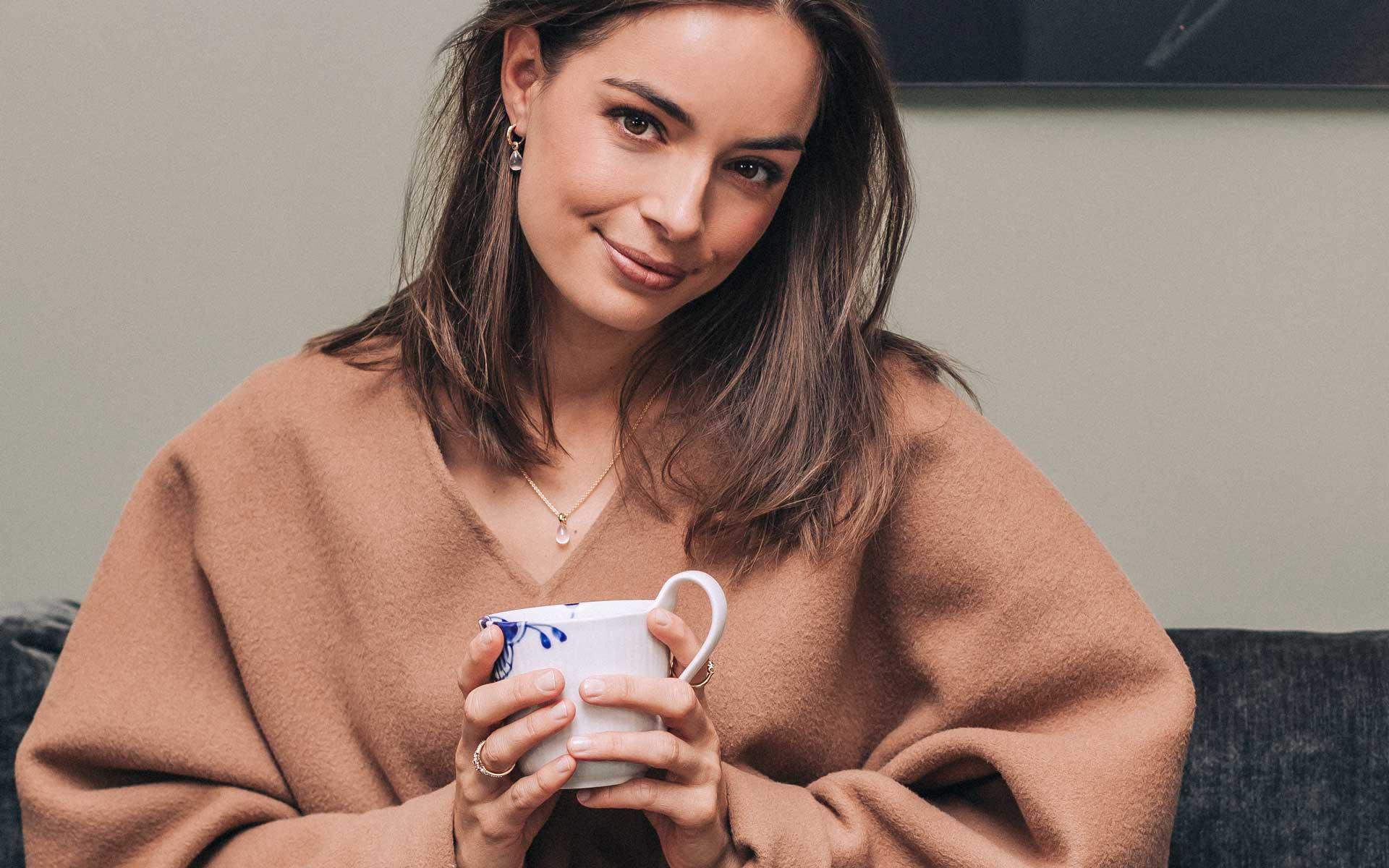 Modell som holder kaffekopp