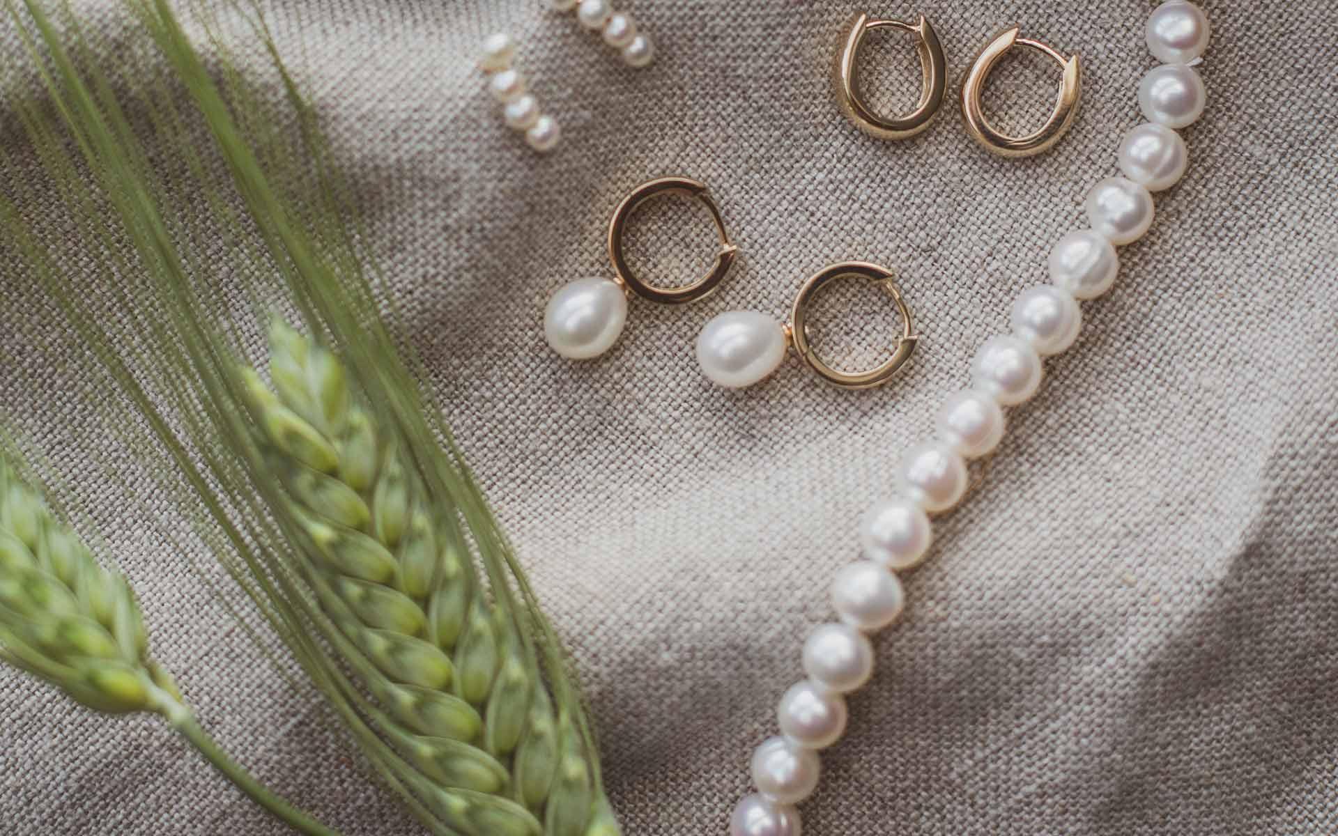Ørepynt i gult gull med hvite perler, og perlekjede